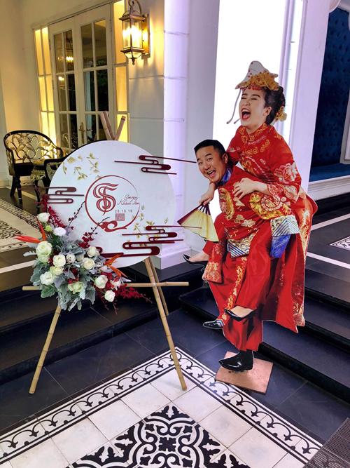 Bảng welcome phía bên ngoài sảnh tiệc có hình ảnh của hai vợ chồng Khánh Tâm mang âm hưởng Trung Hoa và được tô điểm bởi hoa hồng tươi, thiên điểu. Hình ảnh của uyên ương được đặt bên cạnh mang phong cách vui nhộn, hài hước.