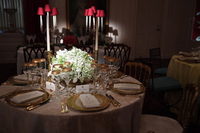 A table is beautifully decorated with rich-looking gold plates, cutlery, candles and a white floral centrepiece