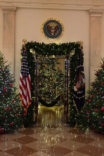 [Caption]aA number of trees with red decorations sit in the grand foyer next to American flags