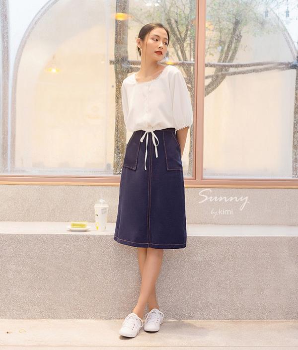 Cũng là chất liệu denim, chân váy hai túi chỉ nổi màu xanh dương có thiết kế đơn giản, dài ngang gối kín đáo, giúp bạn gái thêm nữ tính và thanh lịch.