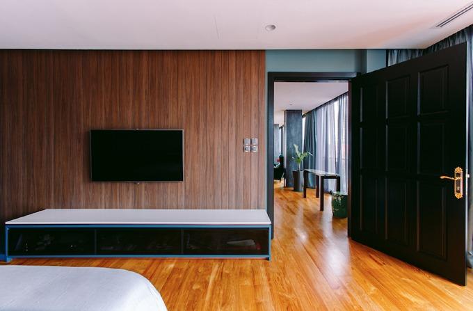 Phòng ngủ chính có nội thất mang sắc xanh dương và xanh lá dịu nhẹ.