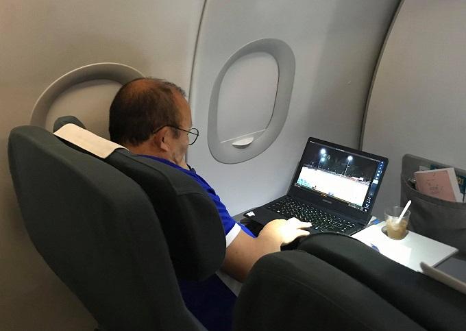 Ông Park xem lại trận đấu trên máy bay. Ảnh: Lâm Thỏa.