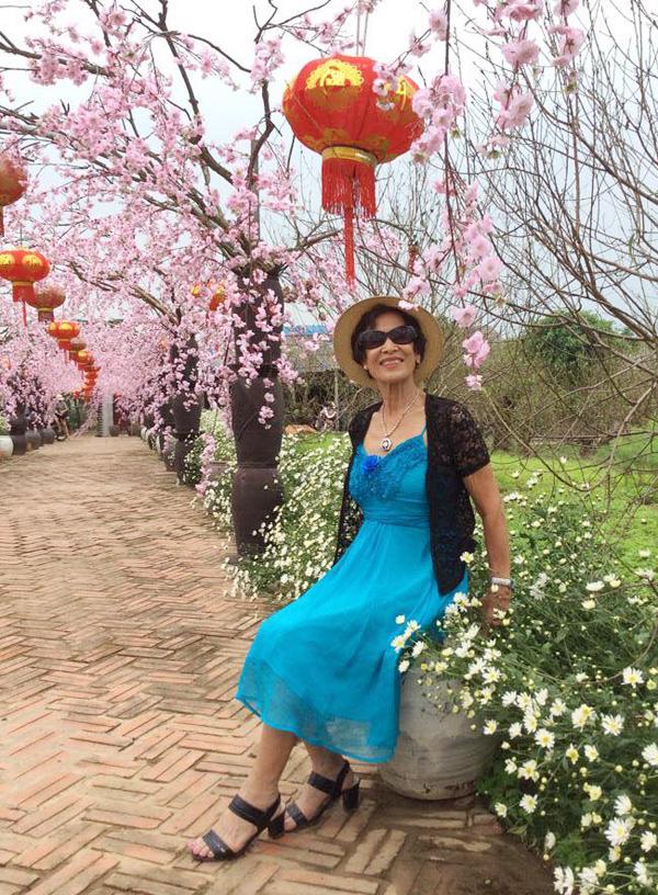 Gần 80 tuổi, cụ bà Hà Nội không ngại mặc váy hai dây màu xanh như thiếu nữ, kết hợp áo ren và sandal cao gót.