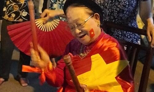 Bà ngoại ca sĩ Nhật Thu khoác cờ, đánh trống cổ vũ tuyển Việt Nam