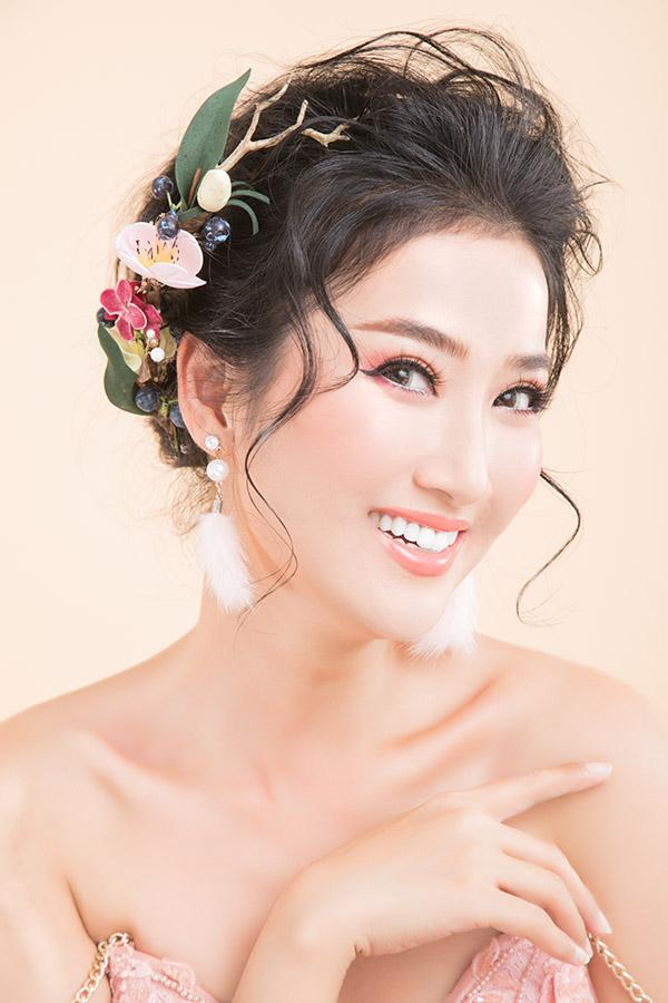 Son môi màu hồng cam giúp Quỳnh Lam hoá thân cô dâu đẹp tự nhiên, sang trọng. Phụ kiện hoa cài đầu tô điểm cho mái tóc và gương mặt thêm nổi bật.