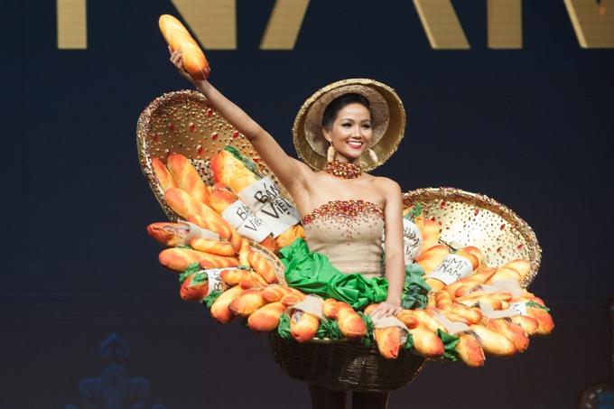 Tối 10/12, HHen Niê trình diễn Bánh mì trong phần thi trang phục truyền thống thuộc khuôn khổ Miss Universe 2018 tại Thái Lan. Người đẹp diện thiết kế lấy cảm hứng từ bánh mì - món ăn đường phố nổi tiếng kết hợp váy quây và nón lá. Chia sẻ với Ngoisao.net, đại diện êkíp của HHen Niê cho biết cô gặp sự cố hỏng mắc gài ngay trước đêm thi khiến phần mô hình bánh mì không được định hình vững chắc như ban đầu.Nhận thấy được sự cố nhưng HHen vẫn tự tin trình diễn. Cô bước đi chậm rãi, giúp một cánh tay cố định tránh hai cái sề (phầnđan mắt thưa, nan thô) không bị đổ về sau. Dù không thể thỏa sức