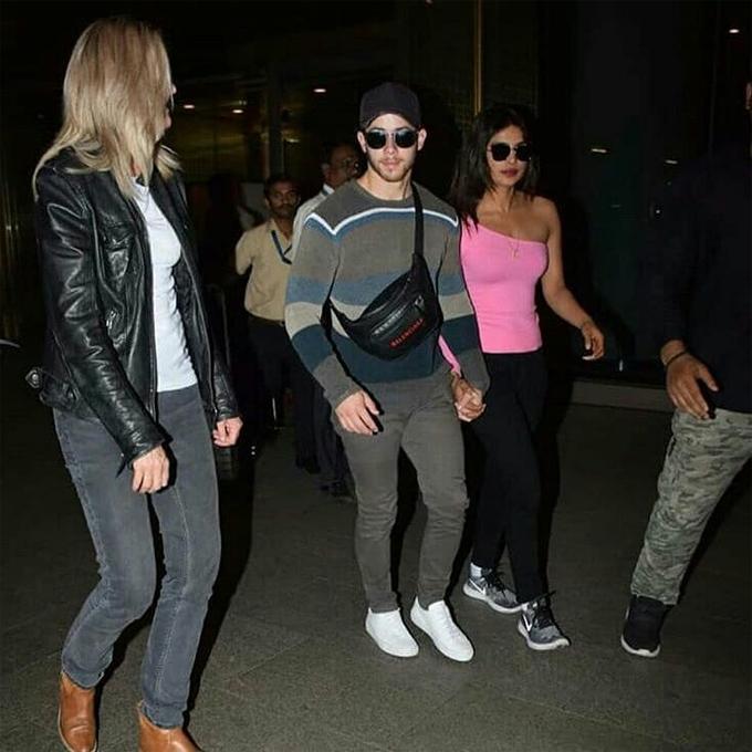 Nick nắm chặt tay vợ trong suốt quãng đường từ sân bay ra xe. Hai người được dàn vệ sĩ và các nhân viên an ninh hộ tống.