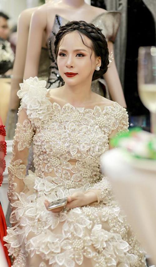 Cô chọn trang sức ngọc trai tương đồng với một trong những chất liệu thiết kế bộ váy. Tone trang điểm nhấn vào mắt và môi tôn nét kiêu sa của người đẹp.
