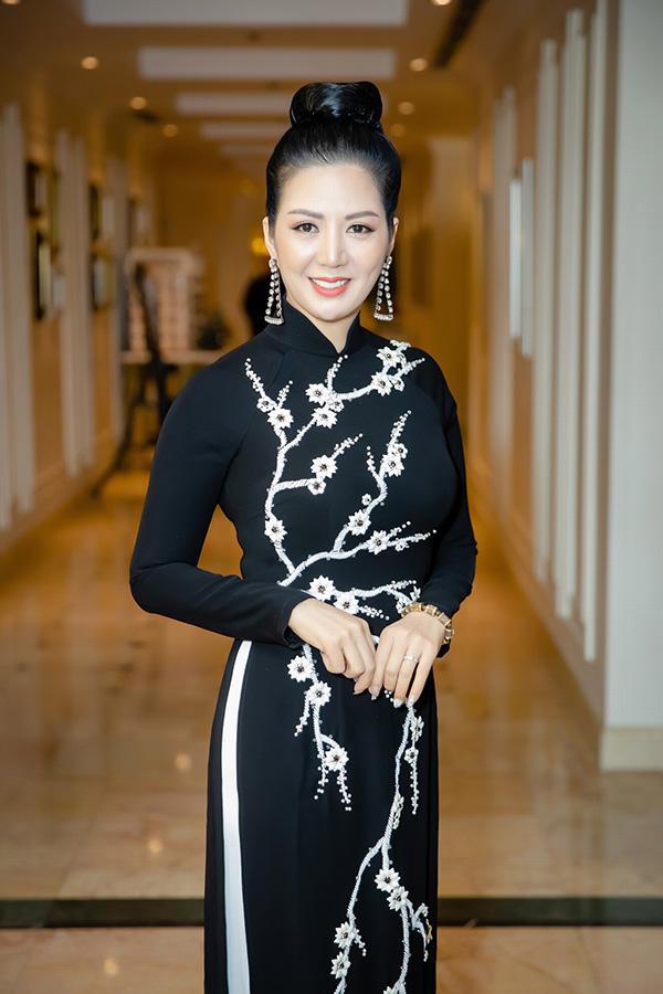Đối lập phong cách với Thu Phương, ca sĩ Đinh Hiền Anh diện áo dài đính hoa 3D kín đáo đến dự họp báo.