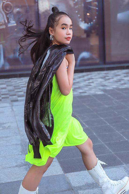 Phong cách cá tính cho các bé gái với váy suông màu nổi đi kèm áo khoác trong suốt, giầy sneaker cao cổ.