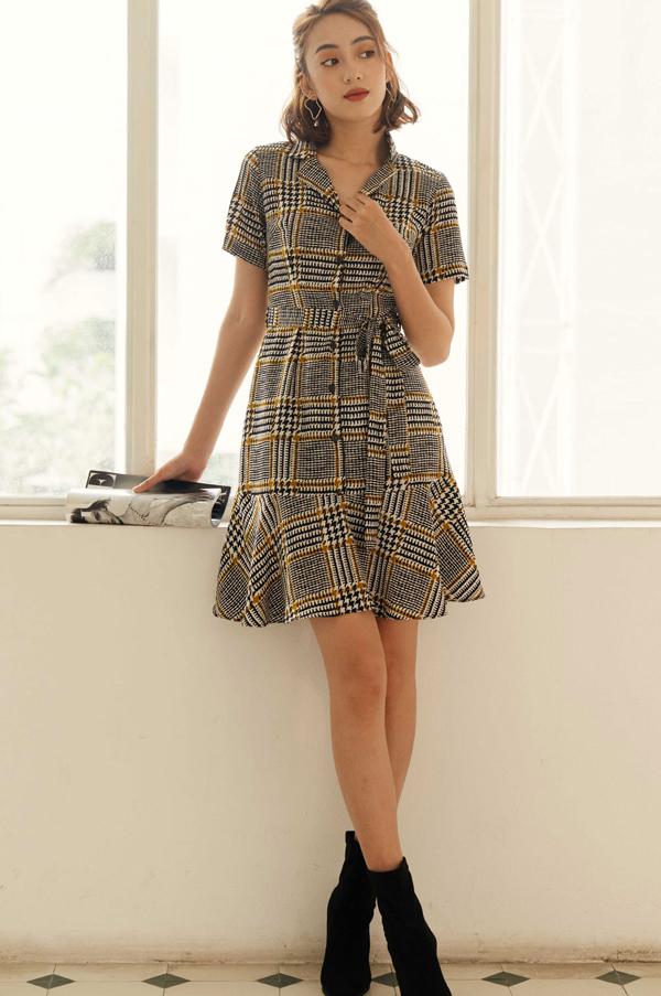 Chiếc váy trênnền vải hoạ tiết caro trở nên sang trọngvới phầnnơ thắt eo và hàng cúc mang tính điểm xuyết. Chi tiết cổ vest cũng góp phần tô đậm vẻ thanh lịch của người mặc.