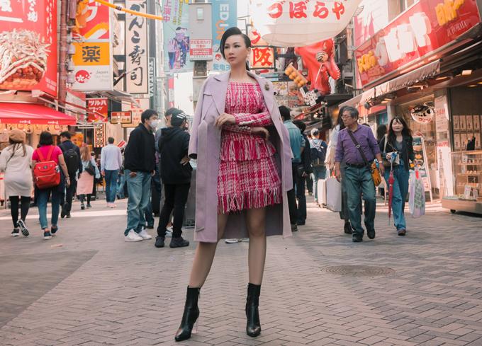 Paris Vũ tạo dáng giữa khung cảnh đường phố Tokyo đông đúc, nhộn nhịp người qua lại.