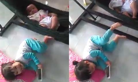Chị gái dùng chân đẩy võng ru em