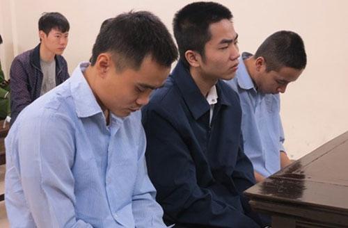 Ba bị cáo (ngồi trên cùng) tại phiên tòa sơ thẩm.