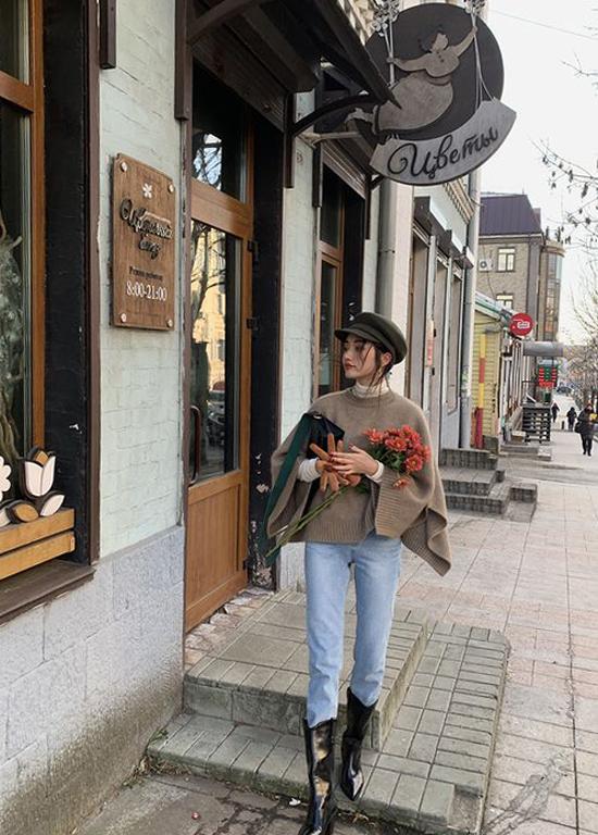 Áo len dáng cape được phối cùng jeans cổ điển, bốt và mũ baker boy giúp set đồ street style của các nàng trở nên bắt mắt hơn.