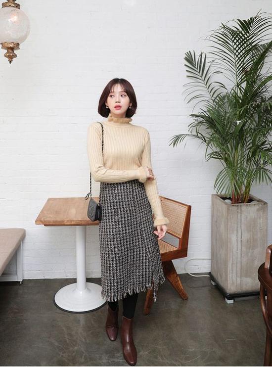 Chân váy vải tweed là sản phẩm được ưa chuộng ở mùa đông năm nay. Trên nền vải bố ấm áp là họa tiết ca rô nhí trẻ trung.