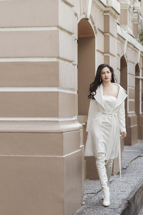 Set đồ white on white gồm váy quây, áo măng tô và bốt cổ cao giúp phái đẹp thể hiện nét gợi cảm, cá tính.