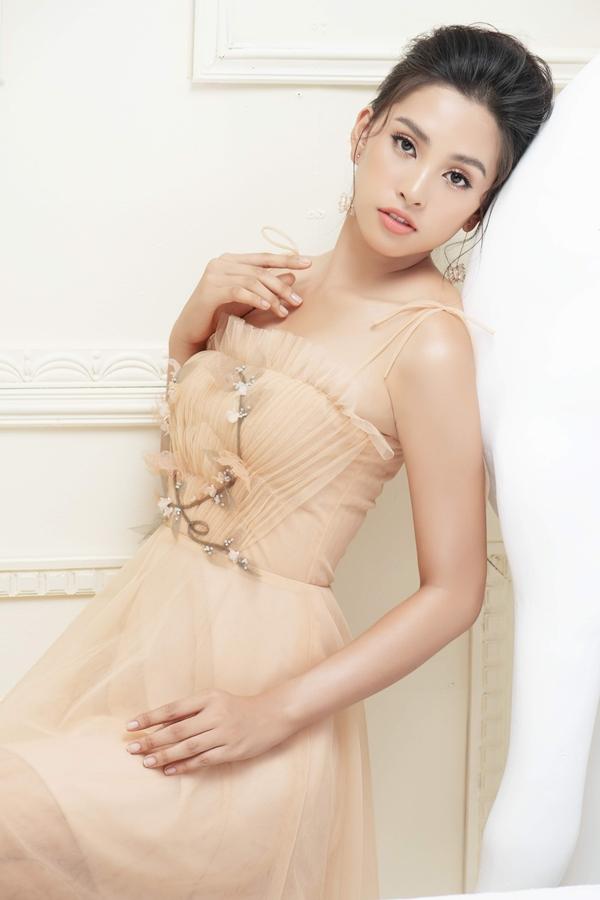 Hoa hậu sinh năm 2000 khoe vai thon với váy hai dây gợi cảm. Trên nền renxếp nếp, nhà mốt ứng dụng họa tiết hoa lá đính kết tỉ mỉ, lạ mắt.