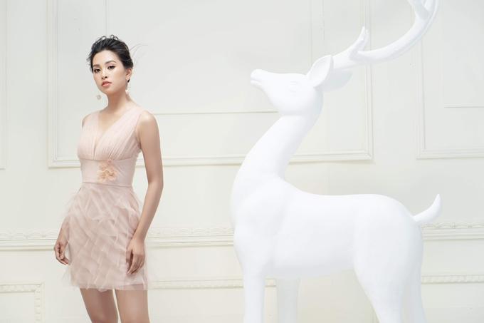 Váy gam hồng pastel ngọt ngào không đơn điệu nhờ phần cổ chữ V xẻ sâu. Họa tiết hoa 3D và những đườngxếpgiúp trang phục thêm hút ánh nhìn.