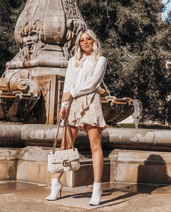 Sơ mi lụa đi cùng chân váy vải tweed, thêm vào đó là phụ kiện đồng điệu sắc trắng sẽ mang lại tổng thể ưa nhìn cho các nàng công sở.