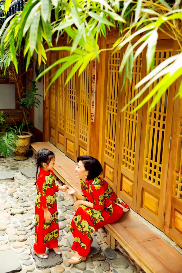 Hai mẹ con Mai Phương vô tư cười đùa, nói chuyện với nhau khi diện trang phục truyền thống in hoạ tiết chú heo.