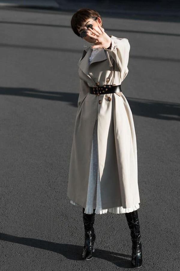 Á hậu Huyền My mang tới sự mới mẻ về hình ảnh với mái tóc tém và lối mix đồ tôn nét cá tính. Áo măng tô màu trung tính được phối cùng váy trắng và phụ kiện bốt da bóng.