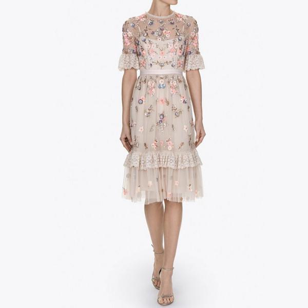 Bộ váy cocktail nhẹ nhàng với họa tiết hoa in nổi đính kim sa góp phần tạo điểm nhấn cho trang phục mà không quá phô trương.