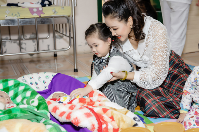 Cô bé tỏ ra thích thú khi chạm tay âu yếm các em bé mồ côi tại trung tâm.