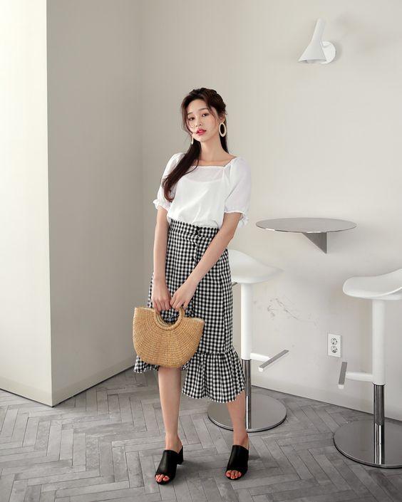 Chân váy ca rô tông màu tương phản đi kèm áo cotton lụa trắng sẽ mang đến nét thanh lịch, trẻ trung cho người mặc.