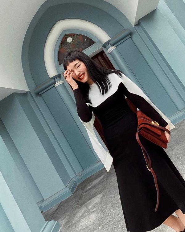 Châu Bùi hiền dịu hơn với mọi ngày khi chọn váy trắng đen kiểu dáng cơ bản để xuống phố. Tuy nhiên cô nàng sành điệu bậc nhất showbiz không quên tạo điểm nhấn cho mình bằng mẫu túi da lộn tôn đỏ burgundy thời thượng.