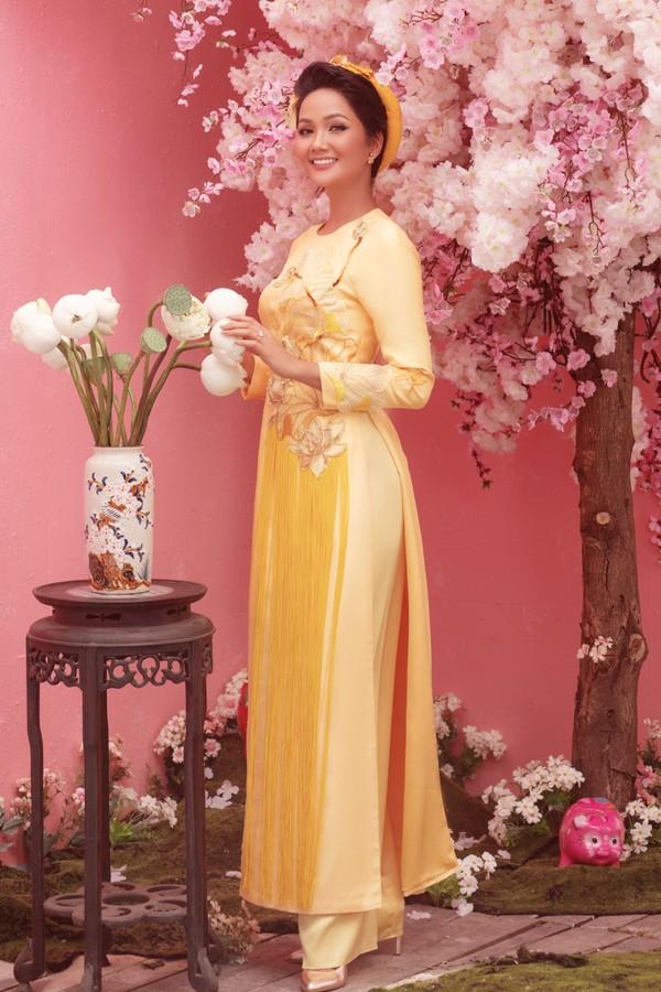 HHen Niê nổi bật với áo dài tông vàng hoàng kim. Mẫu thiết kế của Thủy Nguyễn được chăm chút từ việc chọn chất liệu, áp dụng kỹ thuật thêu, tạo hình hoa nổi và kết tua rua kỳ công.