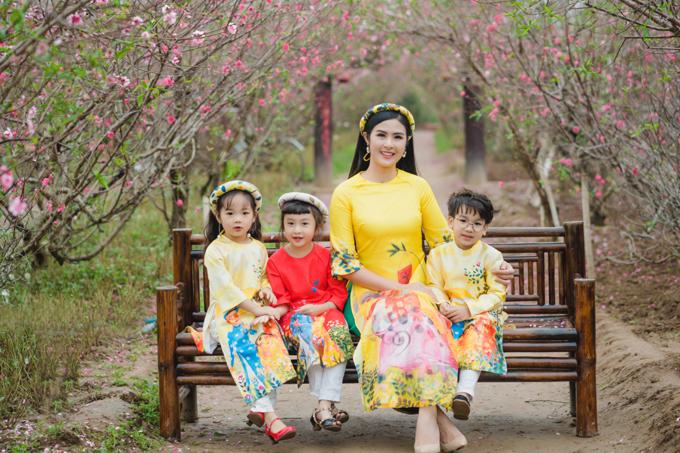 Hoa hậu Việt Nam 2010 cùng các em nhỏ diện áo dài do cô thiết kế trong bộ ảnh Tết.