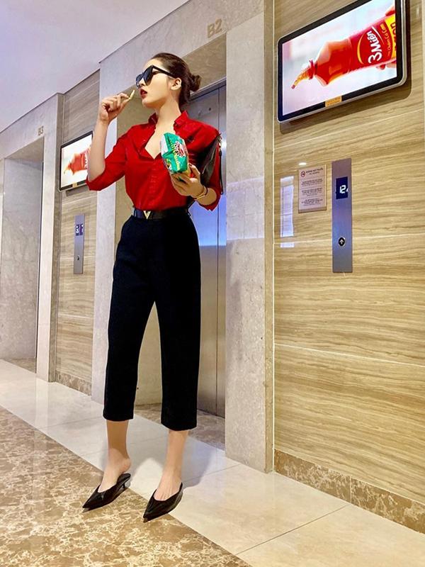 Kỳ Duyên sử dụng áo sơ mi tông màu đỏ tươi - gam màu được ưa chuộng trong dịp Tết với quần ống lửng. Set đồ của hoa hậu trở nên hút mắt hơn nhờ phụ kiện giày mules hợp mốt.