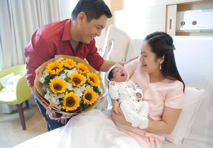 Đức Thịnh ôm bó hoa hướng dương rực rỡ vào tặng vợ, mừng hai mẹ con được về nhà.