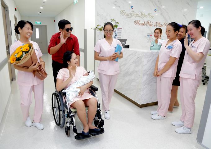 Đức Thịnh đẩy xe đưa vợ và con trai ra về. Cả nhà anh vui vẻ chào tạm biệt các y tá, nhân viên của bệnh viện phụ sản.