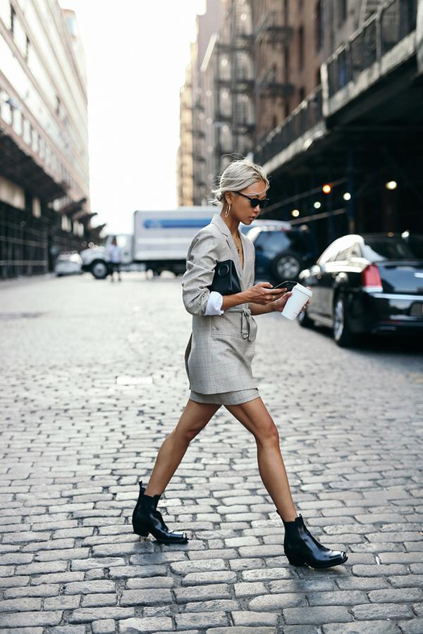 Cltuch, bốt cổ thấp tông đen là các món phụ kiện mang lại sự hoàn hảo cho bộ suit xám gồm blazer và chân váy ngắn.