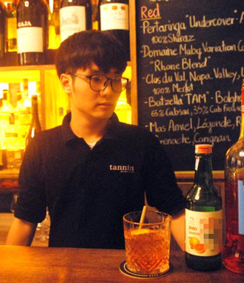 Bartender trong nhà hàng trên phố Hàng Vải bên một trong bốnly cocktail từ soju bưởi hồng-Peace Negroniation -vừa hoàn thành tối 21/2.
