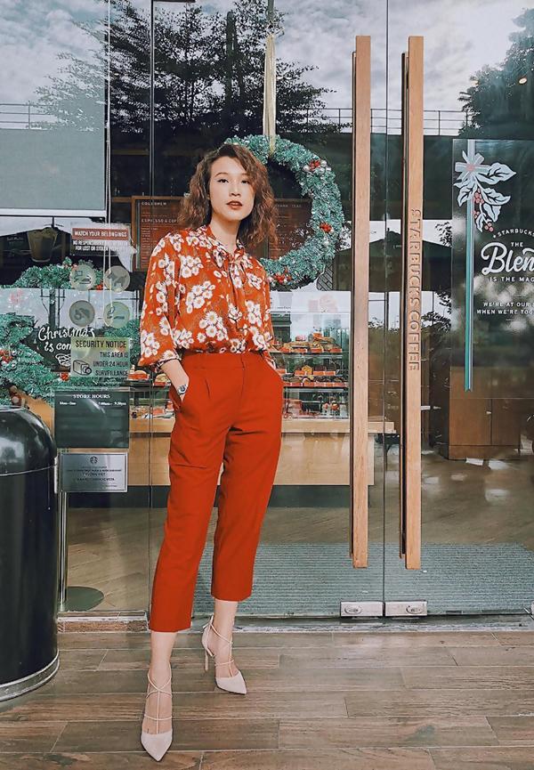 MC Hoàng Oanh nổi bật với set đồ rực rỡ sắc cam gồm áo sơ mi in hoa và quần côn ống lửng. Set đồ này dễ áp dụng cho giới nữ văn phòng bởi kiểu dáng thanh lịch.