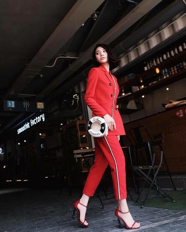Ngoài sắc cam nóng bỏng, tôn đỏ cam và đỏ đậm cũng được các người đẹp Việt nhiệt tình lăng xê. Jolie Nguyễn xây dựng vẻ đẹp hiện đại và năng động cùng suit kẻ sọc. Túi đeo chéo Chanel dáng phao bơi và sandal Saint Laurent là hai món hàng hiệu được người đẹp chọn lựa để hoàn thiện set đồ dạo phố.