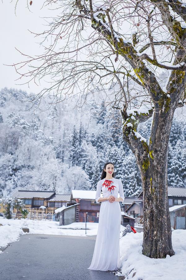 Áo dài cách điệu không cổ lấy điểm nhấn là họa tiết gam đỏ trên ngực giúp gái một con nổi bật khi đứng trước ngôi làng cổ 400 tuổi ở Nhật.