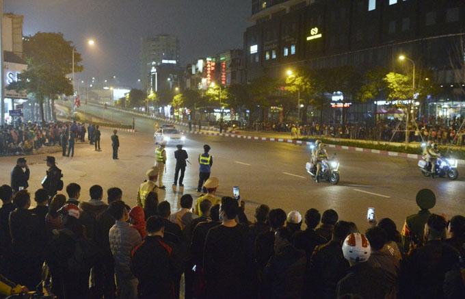 21h30, hàng trăm người dân đứng hai bên đường Trần Duy Hưng chờ đoàn xe Tổng thống Mỹ đi qua. Họ mang theo cờ Việt Nam, cờ Mỹ và cầm điện thoại phát trực tiếp hình ảnh lên Facebook. Hai xe mô tô, một xe ô tô dẫn đoàn của CSGT cũng chờ sẵn tại đây.