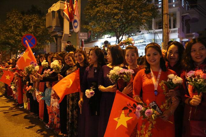 Nhóm phụ nữ cầm hoa, cờ tổ quốc hào hứng đứng đợi sẵn. Ảnh: Phạm Dự.