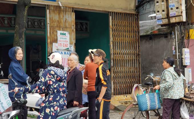 Người dân trong ngõ nhỏ 25 Hoàng Hoa Thám đứng trước cửa nhà nghi can Trịnh Viết Ba kể lại vụ việc. Ảnh: Giang Chinh