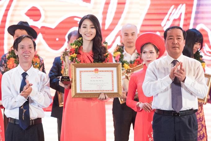 Tiểu Vy rạng rỡ trên sân khấu nhận bằng khen và cúp kỷ niệm. Người đẹp 19 tuổi sinh ra và lớn lên ở Hội An (Quảng Nam). Cô là thí sinh đầu tiên đến từ Hội An đăng quang danh hiệu Hoa hậu Việt Nam vào tháng 9/2018. Sau đó, Tiểu Vy tiếp tục dự thi Miss World và lọt top 30 chung cuộc.