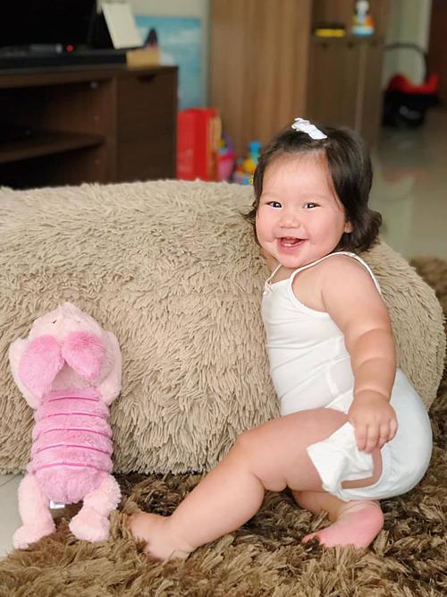 Bé Myla - con gái siêu mẫu Hà Anh cười tít mắt khi đùa nghịch cùng chú lợn hồng.