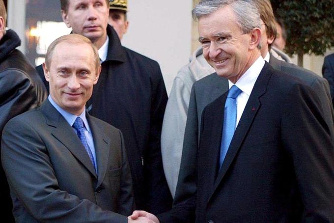 Ông vua hàng hiệubắt tay Tổng thống Nga Vladimir Putin trong chuyến thăm vào năm 2003 của ông Putin tới trang trại trồng nho Chateau Cheval Blanc của LVMH ở Pháp.