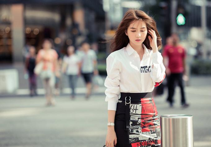Nữ người mẫu trông trẻ trung, thanh lịch với áo sơmi trắng, váy ngắn.