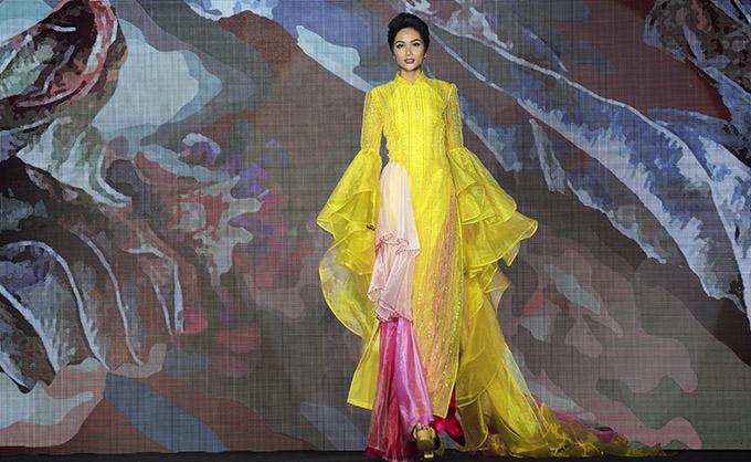 HHen Niê biểu diễn tại một khách sạn 5 sao ở TP HCM. Cô nổi bật trong bộ áo dài vàng, tay áo cách điệu kiểu bèo nhún, phần tà trước có một nửa may dạng xếp tầng như váy dạ hội.