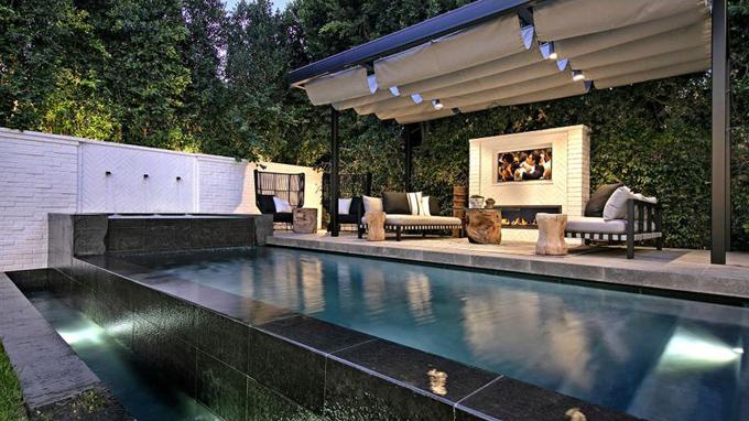 Bể bơi ngoài trời giữa khu vườn tươi xanh và trồng nhiều cây ô-liu.