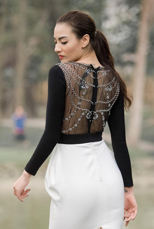 Bà mẹ đơn thân khoe khéo vóc dáng thon thả cùng hình xăm chiếc lông vũ ở phía sau lưng khi catwalk giữa không gian xanh mướt của Công viên Bách Thảo.
